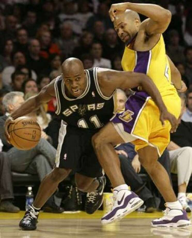 Spurs guard Jacque Vaughn draws a foul as he drives around the Los Angeles Lakers' Derek Fisher in Los Angeles on Dec. 13, 2007. (Danny Moloshok / Reuters)
