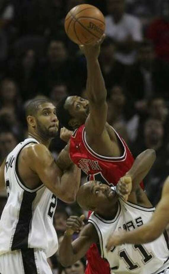 The Chicago Bulls' Adrian Griffin can't reach a rebound between the Spurs' Tim Duncan and Jacque Vaughn on Dec. 26, 2007 at the AT&T Center. (Bahram Mark Sobhani / San Antonio Express-News file photo)