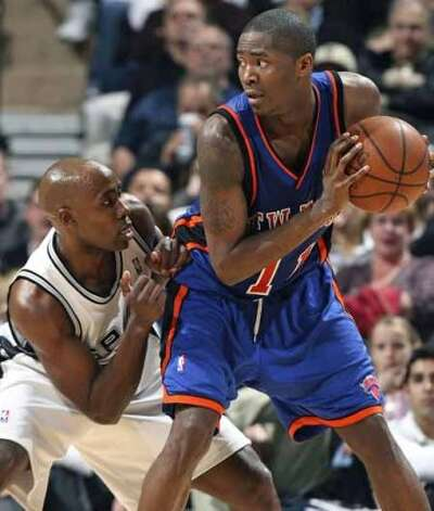 Spurs guard Jacque Vaughn looks at the ball while defending the New York Knicks' Jamal Crawford at the AT&T Center on Jan. 4, 2008. (Tom Reel / San Antonio Express-News)