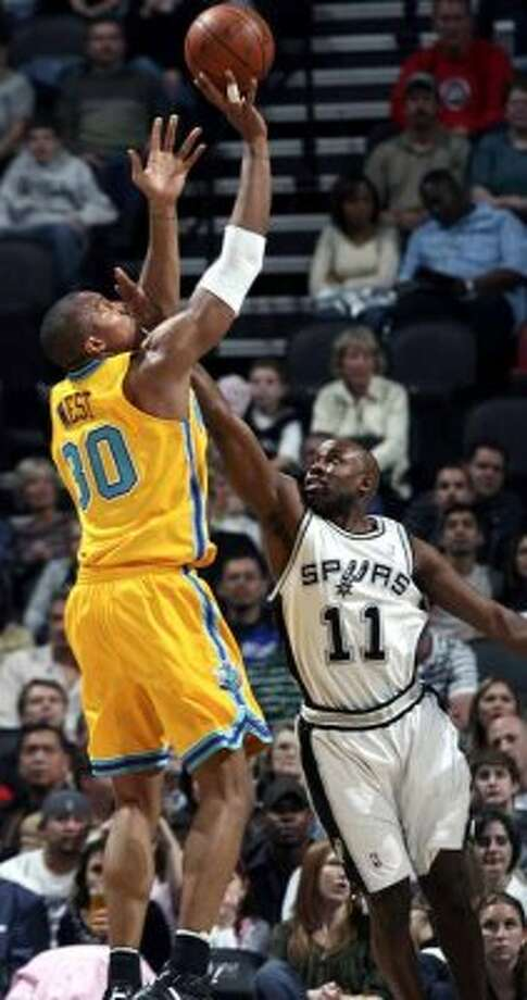 New Orleans Hornets forward David West hits a jumper despite tough pressure from the Spurs' Jackie Vaughn at the AT&T Center on Jan.  26, 2008. (Tom Reel / San Antonio Express-News)