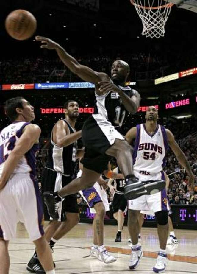 The Spurs' Jacque Vaughn passes to a teammate between the Phoenix Suns' Steve Nash and Brian Skinner in Phoenix on Jan. 31, 2008. The Spurs' Tim Duncan is in the background. (Jeff Topping / Reuters)