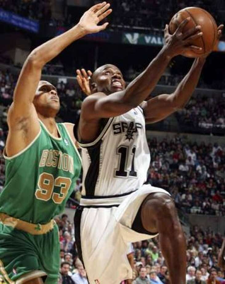 Spurs guard Jacque Vaughn drives to the basket around the Boston Celtics' P.J. Brown on March 17, 2008 at the AT&T Center. (Edward A. Ornelas / San Antonio Express-News)