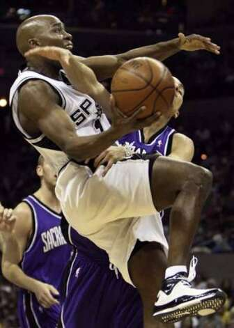 The Sacramento Kings' Kevin Martin reaches in and knocks Spurs guard Jacque Vaughn off his feet on March 21, 2008 at the AT&T Center. (Gloria Ferniz / San Antonio Express-News file photo)