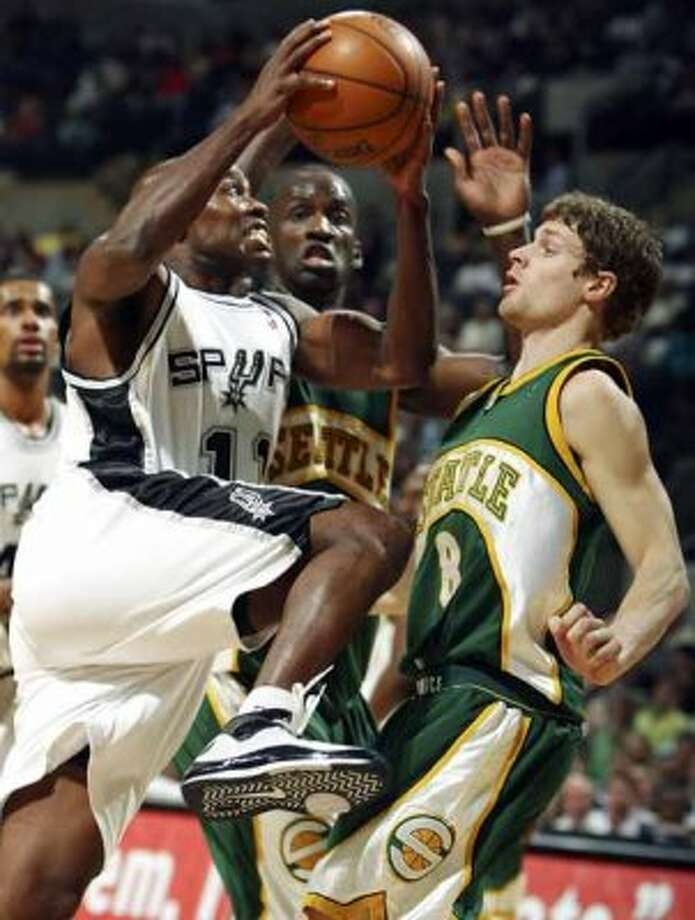 Spurs guard Jacque Vaughn drives to the basket through the Seattle SuperSonics' Luke Ridnour on April 11, 2008 at the AT&T Center. (Edward A. Ornelas / San Antonio Express-News)