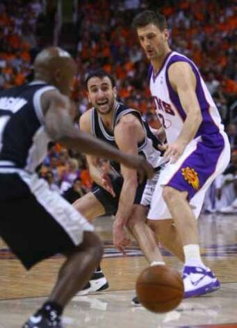 Spurs guard Manu Ginobili passes to teammate Jacque Vaughn as the Phoenix Suns' Gordan Giricek defends him during Game 3 of the first round of the Western Conference playoffs in Phoenix on April 25, 2008. (William Luther / San Antonio Express-News)