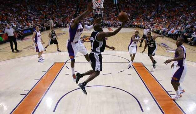 Spurs guard Jacque Vaughn drives past the Phoenix Suns' Amar'e Stoudemire on his way to the hoop during Game 4 of the first round of the Western Conference playoffs in Phoenix on April 27, 2008. (William Luther / San Antonio Express-News)