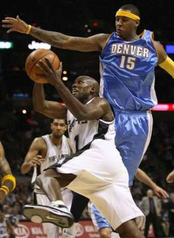 Spurs guard Jacque Vaughn drives under the defense of the Denver Nuggets' Carmelo Anthony on Nov. 19, 2008 at the AT&T Center. (William Luther / San Antonio Express-News)