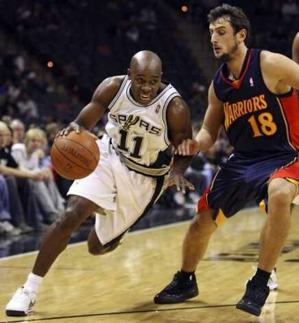 Spurs guard Jacque Vaughn drives around the Golden State Warriors' Marco Belinelli on Dec. 6, 2008 at the AT&T Center. (Edward A. Ornelas / San Antonio Express-News)