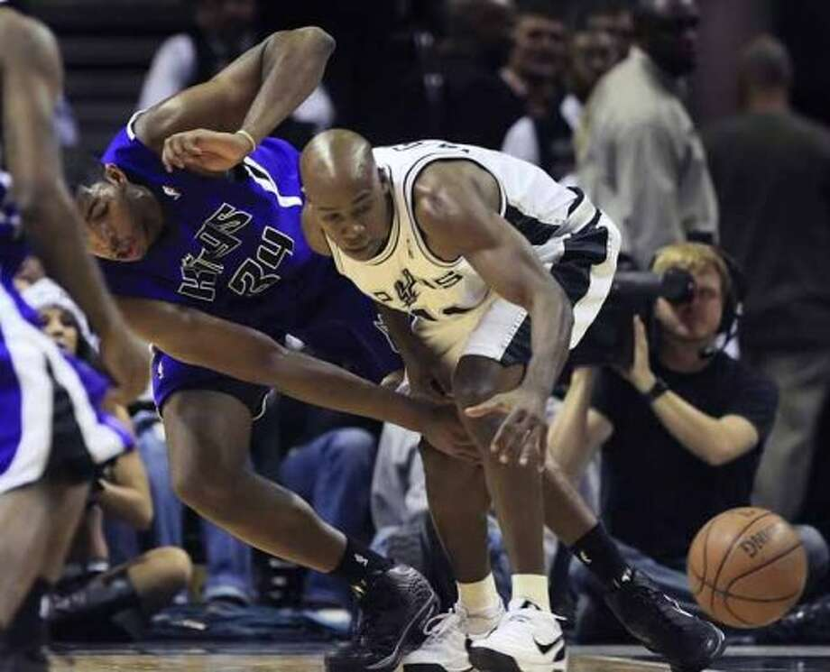 Spurs guard Jacque Vaughn and the Sacramento Kings' Jason Thompson reach for a loose ball on Dec. 22, 2008 at the AT&T Center. (Gloria Ferniz / San Antonio Express-News file photo)