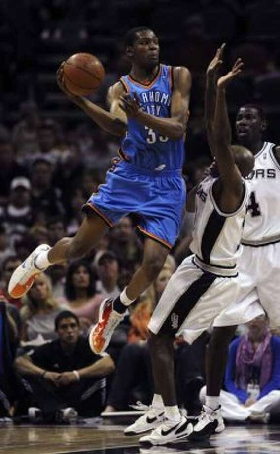 The Oklahoma City Thunder's Kevin Durant passes the ball around the Spurs' Jacque Vaughn and Michael Finley at the AT&T Center on March 31, 2009. (Marc J. Kawanishi / San Antonio Express-News)
