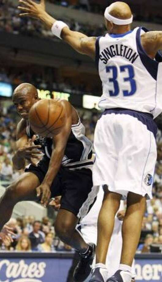 Spurs guard Jacque Vaughn passes around the Dallas Mavericks' James Singleton during Game 3 of the first round of the Western Conference playoffs on April 23, 2009 in Dallas. (Edward A. Ornelas / San Antonio Express-News)
