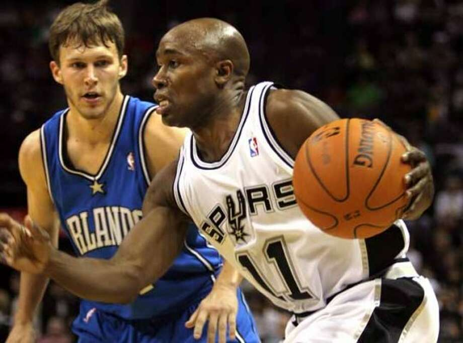 Spurs guard Jacque Vaughn drives against the Orlando Magic's Travis Diener at the AT&T Center on Oct. 14, 2006. (Bob Owen / San Antonio Express-News)