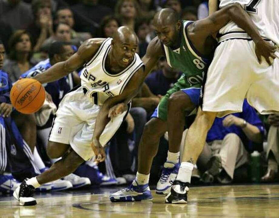 Spurs guard Jacque Vaughn tries to free himself from the defense of Anthony Johnson on Nov. 24, 2006 at the AT&T Center. (Bahram Mark Sobhani / San Antonio Express-News file photo)