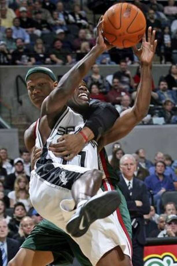 Spurs guard Jacque Vaughn is yanked away from a layup by the Milwaukee Bucks' Charlie Villanueva at the AT&T Center on Dec. 26, 2006. (Tom Reel / San Antonio Express-News)