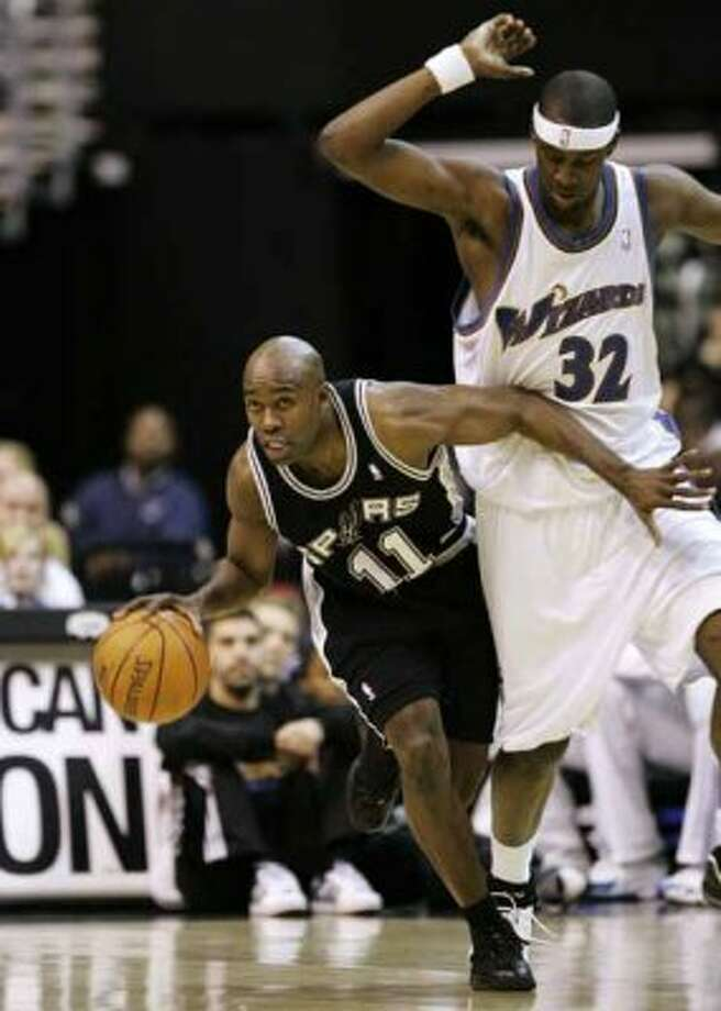 Spurs guard Jacque Vaughn drives beneath the Washington Wizards'  Andray Blatche in Washington on Feb. 7, 2007. (Haraz N. Ghanbari / Associated Press)