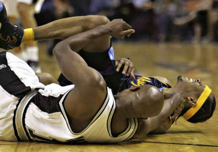 The Denver Nuggets' Allen Iverson grimaces after colliding with Spurs guard Jacque Vaughn while the both scrambled for a loose ball on Feb. 20, 2007 at the AT&T Center. (Bahram Mark Sobhani / San Antonio Express-News file photo)