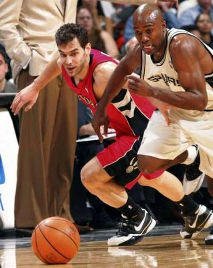 Spurs guard Jacque Vaughn races for the ball against the Toronto Raptors' Jose Calderon at the AT&T Center on on Feb. 26, 2007. (Jerry Lara / San Antonio Express-News)