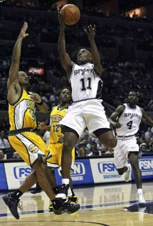 Spurs guard Jacque Vaughn gets a flying layup against the Seattle SuperSonics' Earl Watson at the AT&T Center on April 3, 2007. (Tom Reel / San Antonio Express-News)