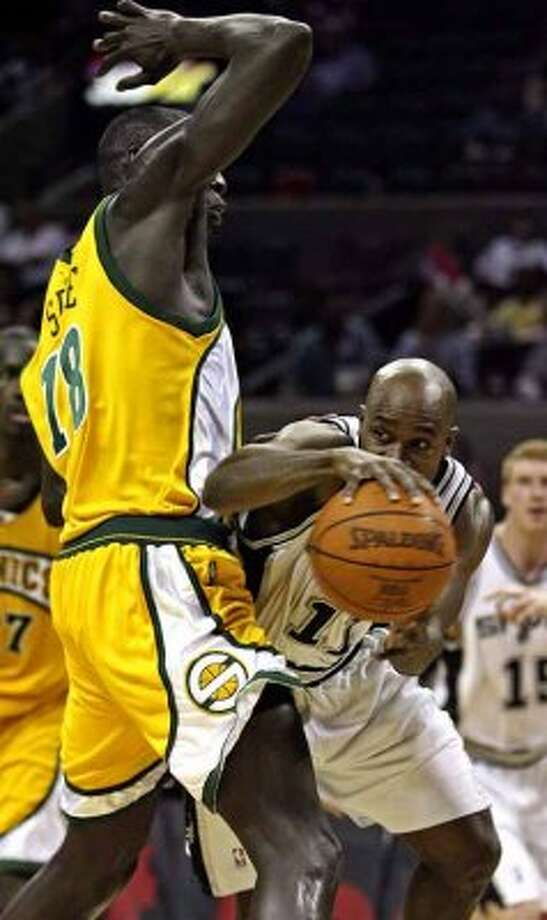 Spurs guard Jacque Vaughn gets the ball out of the lane after driving into the Seattle SuperSonics' big men at the AT&T Center on April 3, 2007. (Tom Reel / San Antonio Express-News)