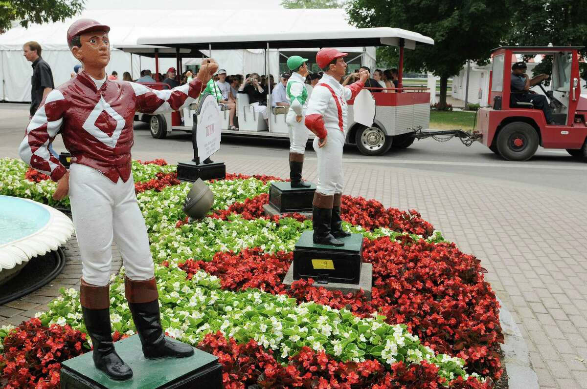 Statues of jockeys are seen a visitors head out for a tour of the back stretch aboard covered cart during the 32nd annual Open House a the Saratoga Race Course on Sunday, July 15, 2012 in Saratoga Springs, NY. The Saratoga racing season starts this Friday. The statues are painted in the silks colors of winners of various races from past Saratoga seasons. (Paul Buckowski / Times Union)