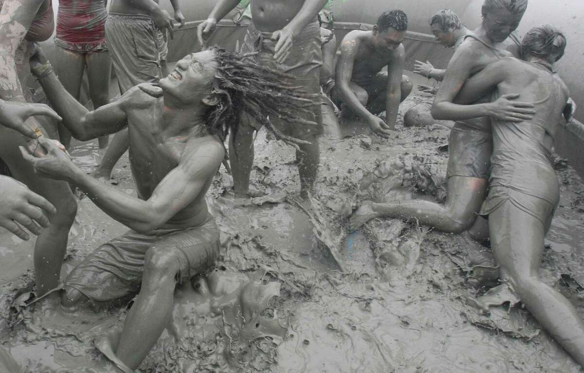 Tourists play with the mud during the 15th annual mud festival on Daecheon Beach in Boryeong, South Korea, Sunrday, July 15, 2012. The festival features mud wrestling, mud sliding and mud king contest.