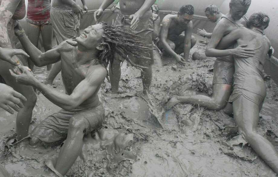 Tourists play with the mud during the 15th annual mud festival on Daecheon Beach in Boryeong, South Korea, Sunrday, July 15, 2012. The festival features mud wrestling, mud sliding and mud king contest. Photo: Ahn Young-joon, AP / AP