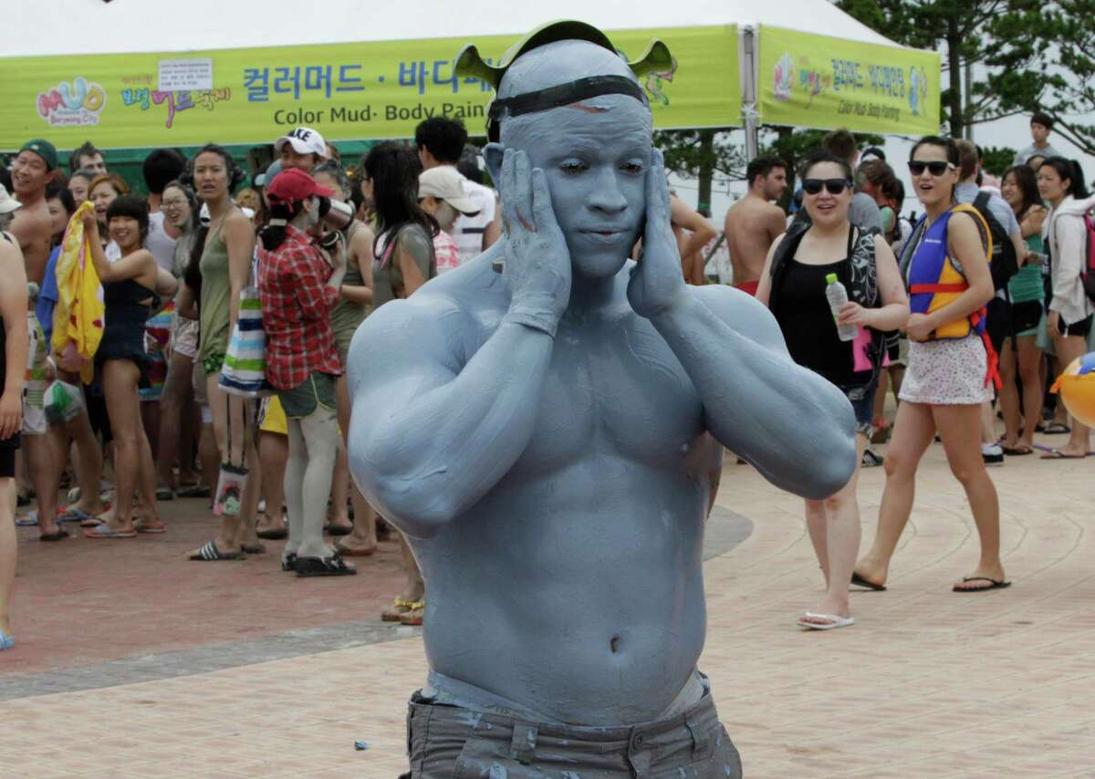 A tourist with his body painted with colored mud, strolls during the 15th annual mud festival on Daecheon Beach in Boryeong, South Korea, Sunrday, July 15, 2012. The festival features mud wrestling, mud sliding and mud king contest.