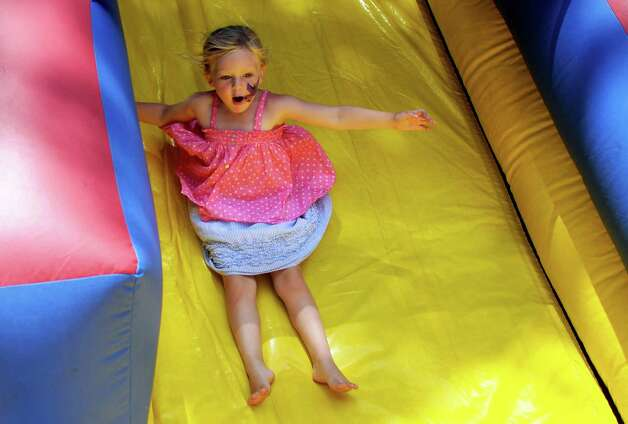 Rowan Tanner, 4, goes down an inflatable slide during the 42nd annual River Ramble at Pinkney Park in Rowayton on Saturday, July 14, 2012. Photo: Lindsay Niegelberg / Stamford Advocate