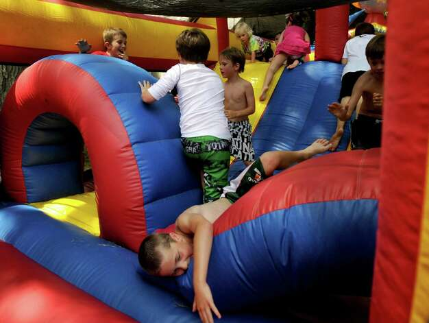 Kids race through an inflatable obstacle course during the 42nd annual River Ramble at Pinkney Park in Rowayton on Saturday, July 14, 2012. Photo: Lindsay Niegelberg / Stamford Advocate