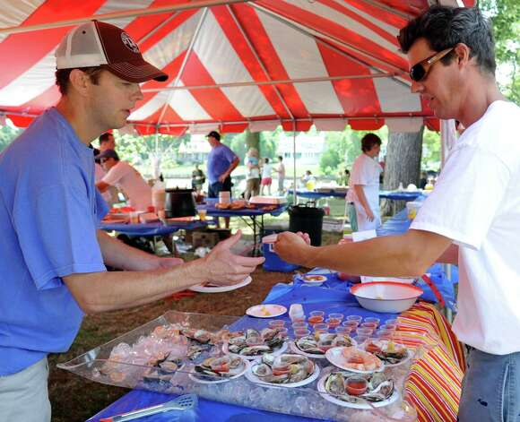 Gardner Gray, right, buys oysters, clams and shrimp from Rick Klein during the 42nd annual River Ramble at Pinkney Park in Rowayton on Saturday, July 14, 2012. Photo: Lindsay Niegelberg / Stamford Advocate