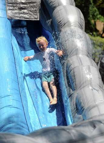 A boy enjoys an inflatable water slide during the 42nd annual River Ramble at Pinkney Park in Rowayton on Saturday, July 14, 2012. Photo: Lindsay Niegelberg / Stamford Advocate