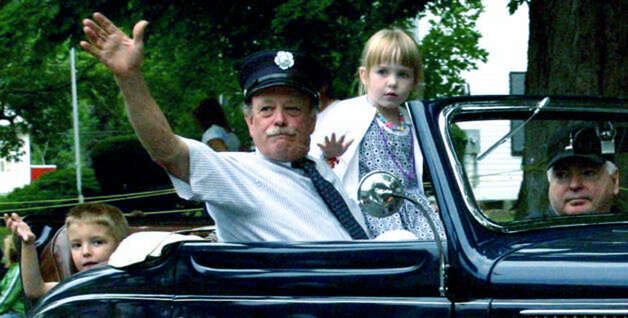 First Selectman Bill Stuart of Bridgewater waves to the crowd as he rides in a townparade with his grandchaildren. At the wheel is George Allingham, formerly a longtime friend of Mr. Stuart. Photo: Walter Kidd
