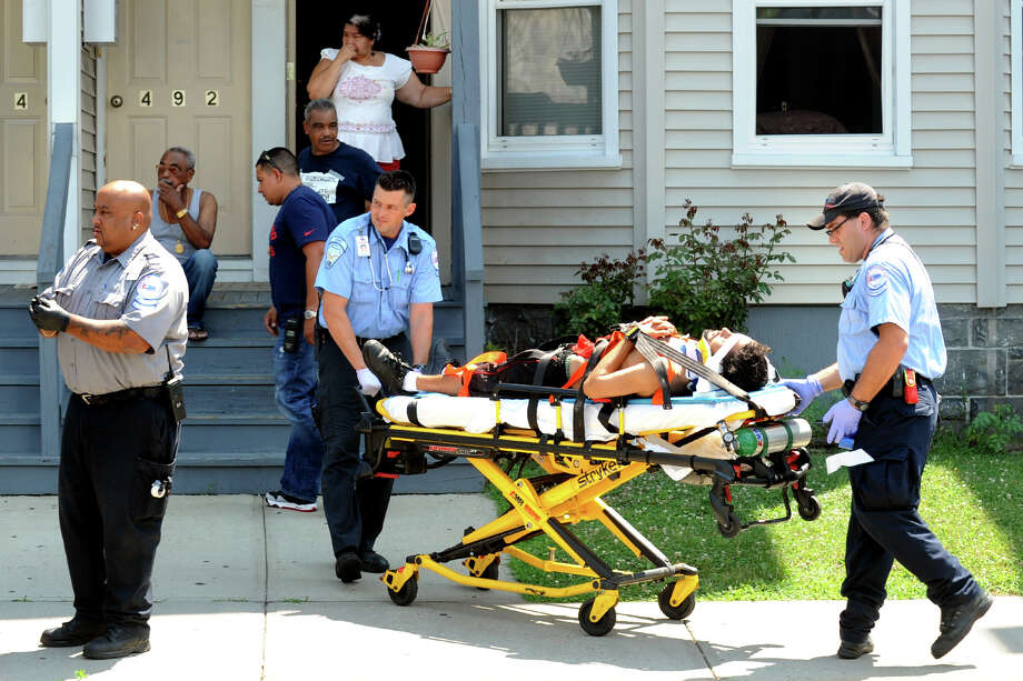 An unidentified man is moved to an ambulance at the scene of a shooting on Brooks Street, in Bridgeport, Conn. on Monday, July 16th, 2012. Photo: Ned Gerard / Connecticut Post