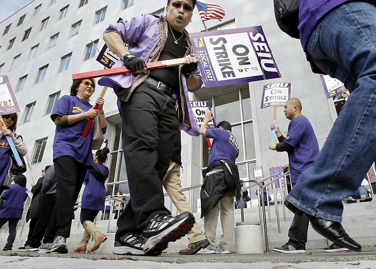 Protesters paraded in front of the Hall of Justice in San Francisco, Calif. where they say they shut down many Superior Courts. Court workers with SEIU Local 1021 walked off the job Monday July 16, 2012 to protest a cut in pay and a lack of financial information from the state to negotiate a new contract.