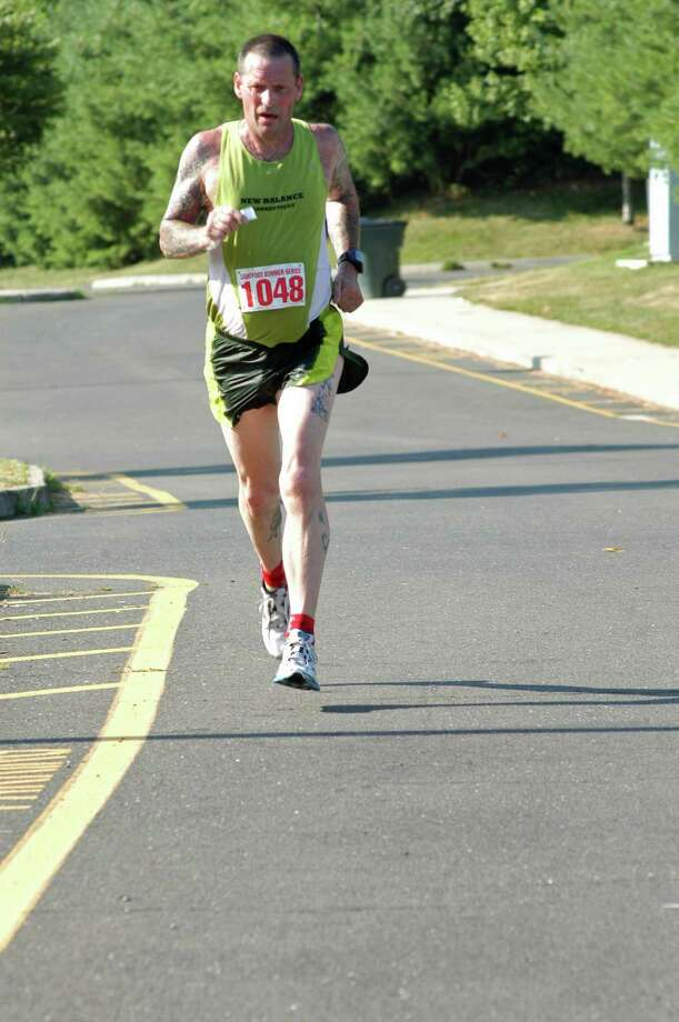 George Buchanan, 54, of Shelton, won the Lightfoot Running Series seven-mile race on Saturday July 14, 2012 with a time of 44:36 at Brien McMahon High School in Norwalk, Conn. Photo: Andy Hutchison