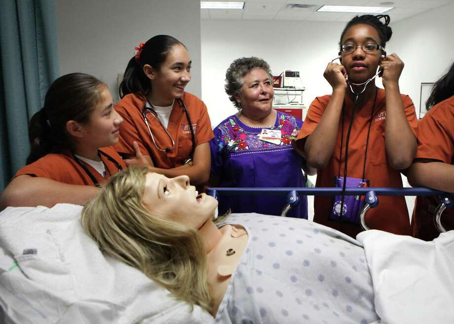 Jaylen McDaniel, right, playing the role of a nurse, adjusts her stethoscope before examining a simulation mannequin as Irene Gomez, left to right, April Gomez and Dr. Norma Martinez Rogers, acting as family members of the patient, look on.  A group of 14 year old girls from low-income parts of South and East San Antonio to experience nursing school at UT Health science Center working on simulation mannequins. Dr. Martinez Rogers is a teacher at the UTHSC San Antonio Nursing School. Monday, July 16, 2012. Photo: BOB OWEN, San Antonio Express-News / © 2012 San Antonio Express-News