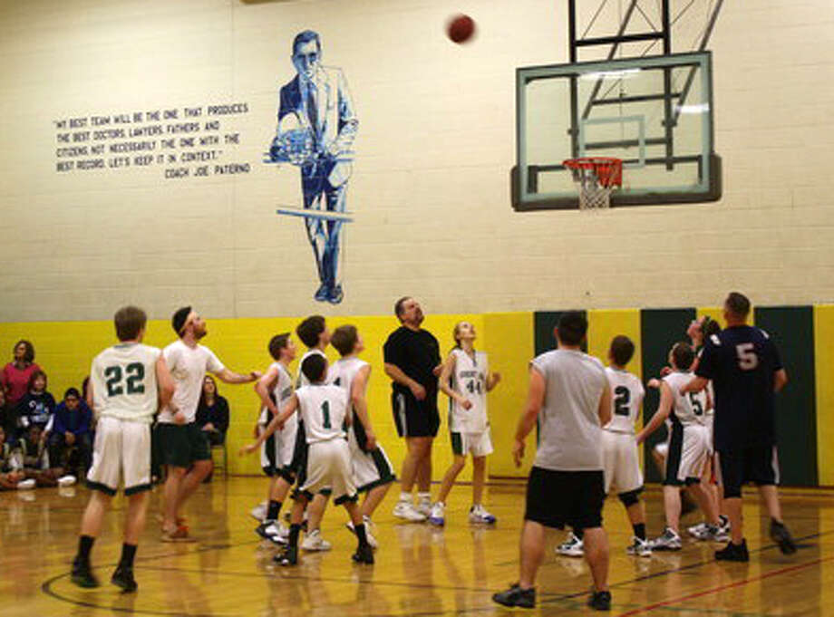 A mural of disgraced former Penn State football coach Joe Paterno is seen on the gym wall during the students vs. teachers basketball game at Great Oak Middle School  in Oxford, Conn. in 2011. The decision was made recently and the paint-over will take place before school resumes, said Board of Education chairwoman, Paula Guillet. Photo: Paul Singley, Oxford.Patch.com