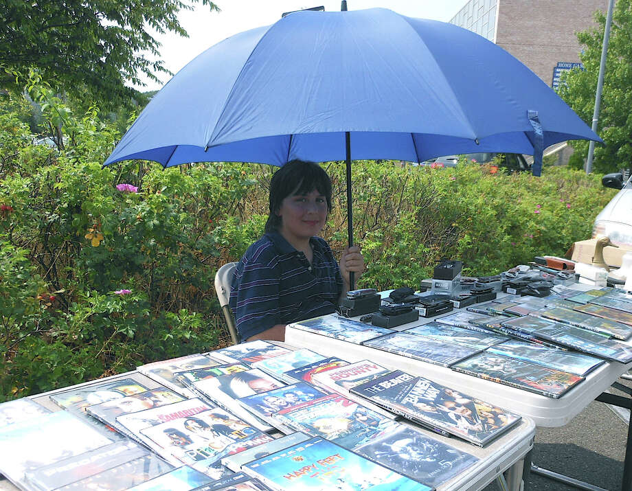 Tyler Gosbin tries to stay cool under a large umbrella while selling DVDs Sunday at Fairfield Ludlowe High School's flea market. Photo: Mike Lauterborn / Fairfield Citizen contributed