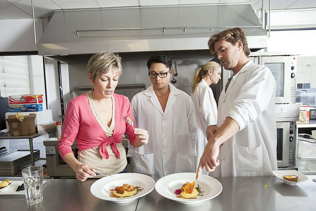 Mattson Executive Vice President of Sales and Marketing Barb Stuckey, left, taste tests a 48-hour brined southern-style fried chicken with chow-chow, pickled sea beans, and heritage corn grits developed by Food Technologist Paolo Beltran, center, and Senior Food Technologist Peter Stearns, right, at the company's laboratory in Foster City.