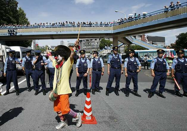 "An anti-nuclear protester dressed as a clown is watched by police officers during a rally in downtown Tokyo Monday, July 16, 2012. Tens of thousands of people gathered at a Tokyo park, demanding ""Sayonara,"" or goodbye, to nuclear power as Japan prepares to restart yet another reactor, and expressed outrage over a report that blamed culture on the Fukushima disaster. Photo: Koji Sasahara, Associated Press"