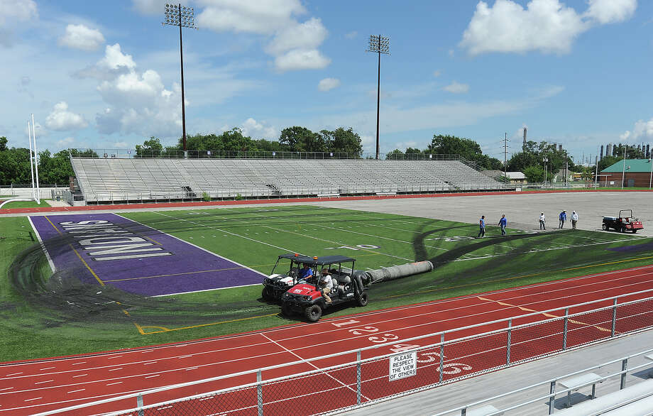 Crew members haul off rolls of turf from the Port Neches-Groves' football field on Monday. Covered under an eight-year warranty, the replacement is due to premature wearing. The new field is expected to be complete before season practice begins. Photo taken Monday, July 16, 2012 Guiseppe Barranco/The Enterprise Photo: Guiseppe Barranco
