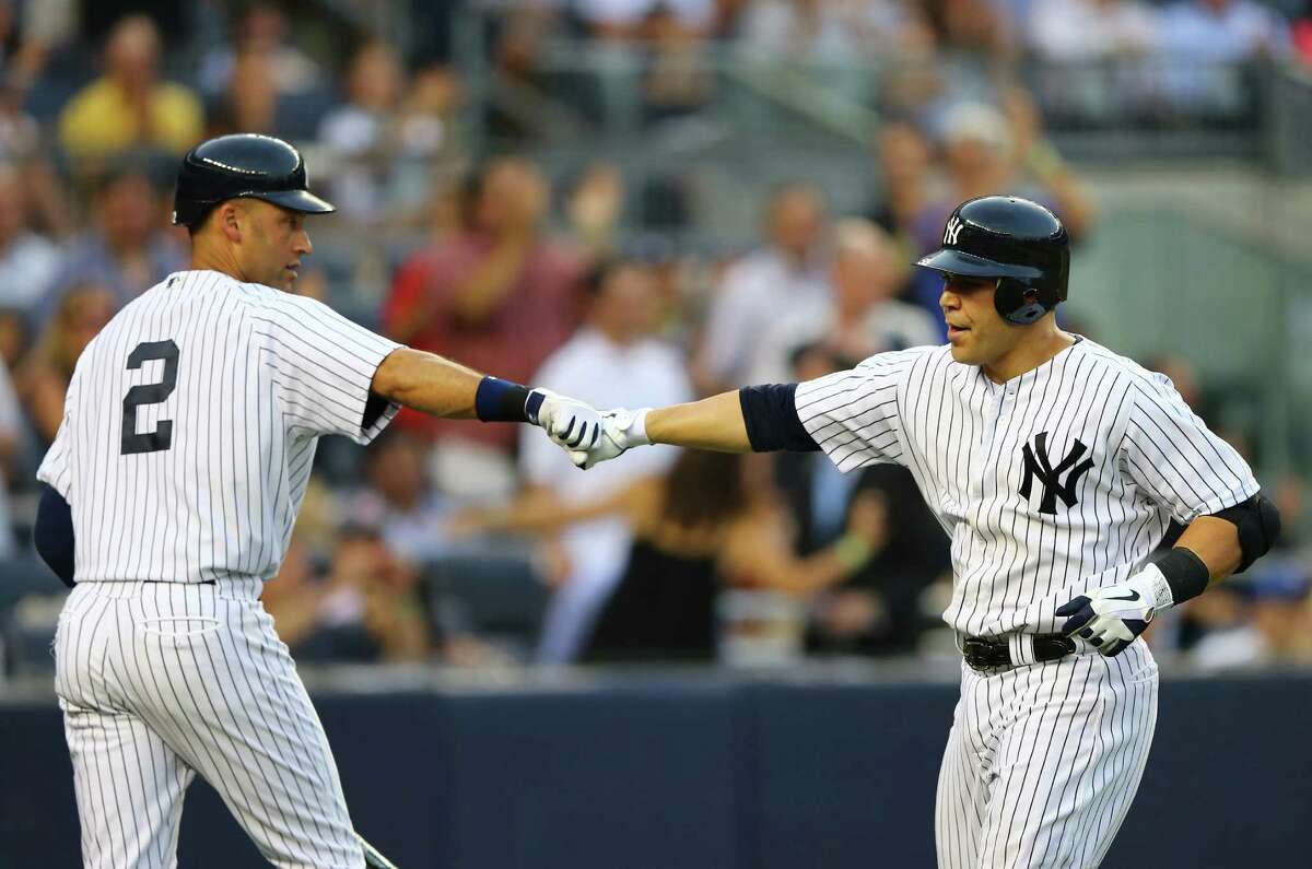 NEW YORK, NY - JULY 16: Russell Martin #55 of the New York Yankees celebrates his home run with Derek Jeter #2 during their game against the Toronto Blue Jays on July 16, 2012 at Yankee Stadium in the Bronx borough of New York City. (Photo by Al Bello/Getty Images)
