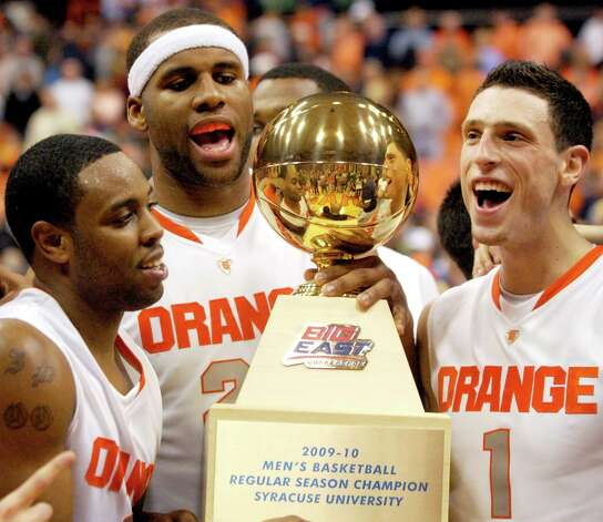 FILE - This March 2, 2010 file photo shows Syracuse basketball players, from left,  Scoop Jardine, Arinze Onuaku, and Andy Rautins, celebrating with the Big East trophy after defeating St. John's 85-66 in an NCAA college basketball game in Syracuse, N.Y.  The Big East has reached an agreement with Syracuse University, allowing the Orange to leave the league a year early for the Atlantic Coast Conference. (AP Photo/Kevin Rivoli, File) Photo: Kevin Rivoli