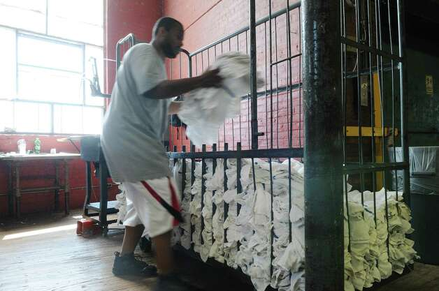 Morgan Linen Service employee Terrence Hampton places cleaned bundled bar mops into a cart  on Thursday, July 12, 2012 in Menands, NY.  The company is celebrating 125 years in business.  (Paul Buckowski / Times Union) Photo: Paul Buckowski