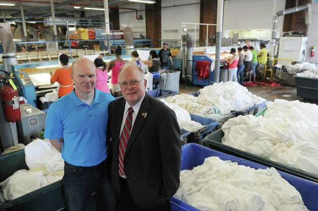 Walker Morgan, left, plant manager of Morgan Linen Service and his father, George Morgan, chairman of board, pose for a photograph on Thursday, July 12, 2012 in Menands, NY.  The company is celebrating 125 years in business.  (Paul Buckowski / Times Union) Photo: Paul Buckowski