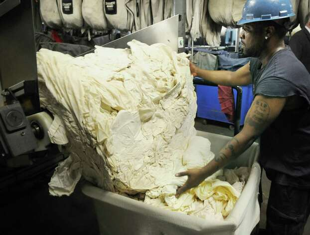 Adam Spencer, an employee at Morgan Linen Service gathers laundry as it comes out of a continuous batch washer  on Thursday, July 12, 2012 in Menands, NY.  The machine holds 1,800 to 2,000 pounds of laundry.  The company is celebrating 125 years in business.  (Paul Buckowski / Times Union) Photo: Paul Buckowski