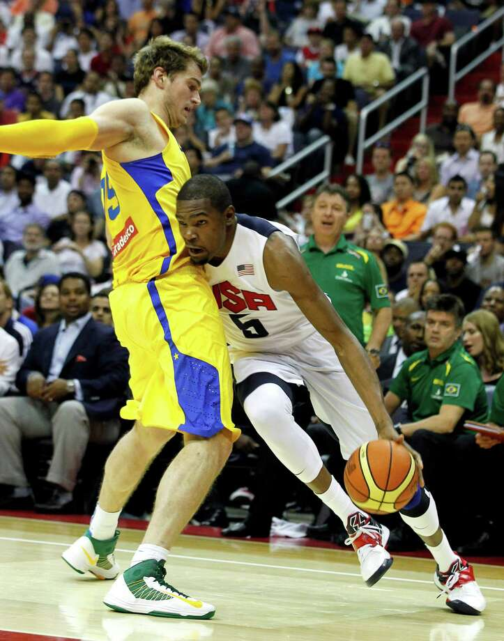 Team USA guard Kevin Durant, right, tries to get past Brazil's Tiago Splitter during the first half of an Olympic men's exhibition basketball game, Monday, July 16, 2012, in Washington. (AP Photo/Alex Brandon) Photo: Alex Brandon, Associated Press / AP