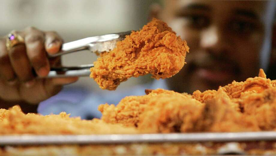 FILE - In this Monday, Oct. 30, 2006 file photo, a Kentucky Fried Chicken employee uses tongs to hold up an sample of the company's trans fat-free Extra Crispy fried chicken in New York.  New York City now has hard evidence that its ban on trans fat in restaurant food made a meaningful dent in people's consumption of the artery clogger and wasn't just replaced with another bad fat. The findings being published Tuesday, July 16, 2012 have implications beyond heart health, suggesting another strategy to curb the nation's obesity epidemic fueled by a high-calorie, super-sized environment. (AP Photo/Kathy Willens, File) Photo: Kathy Willens