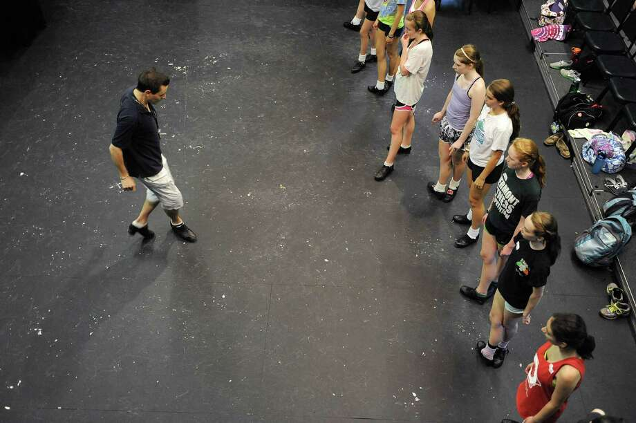 Instructor Marcus Maloney from Ireland shows students a step during a class at the Camp Rince Ceol, an Irish dance camp, on Monday, July 16, 2012 at  Union College in Schenectady, NY.  The camp runs a week long and there are three camps held over the next three weeks.  This is the 13th year of the camp, the last seven years at Union College.  The camp was started by Sheila Ryan-Davoren and her husband Tony Davoren, who were both members of the group River Dance in the mid to late 90's.  Along with Irish dance classes students take classes in classical ballet, Irish language, Yoga and Irish music history.  This first week has 130 students, some international.  The instructors come from the U.S., Australia, Ireland and Scotland.  Students range in age from 8 to 18.    (Paul Buckowski / Times Union) Photo: Paul Buckowski