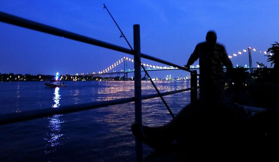 Fishermen hang out  on the Detroit River  following a bomb threat that closed  the Ambassador Bridge to Canada  Monday, July 16, 2012. Someone phoned in a threat from the U.S. side of the busy international border crossing around 7:20 p.m. Photo: Elizabeth Conley, Associated Press